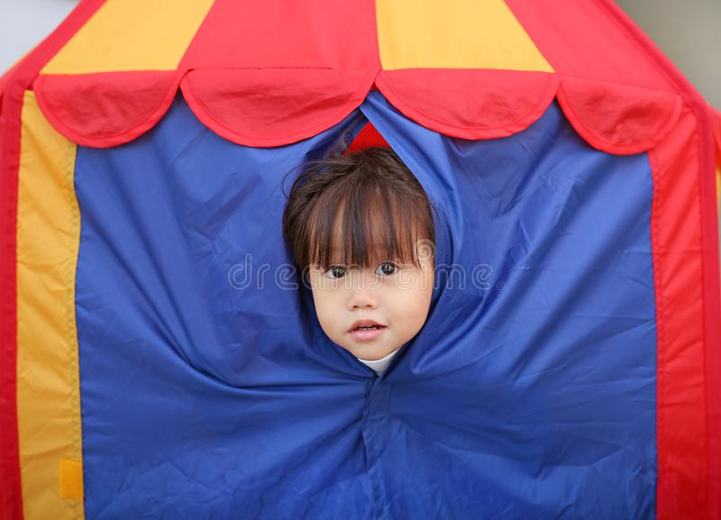 Cute little child girl playing hiding in a kid`s tent stock images