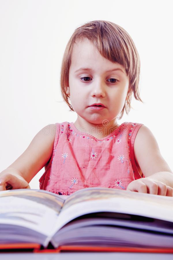 Cute little child girl is reading a book science, development, stock images