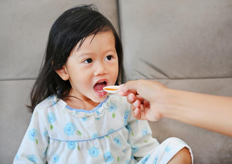 Cute little Child girl receiving pill at home stock photo