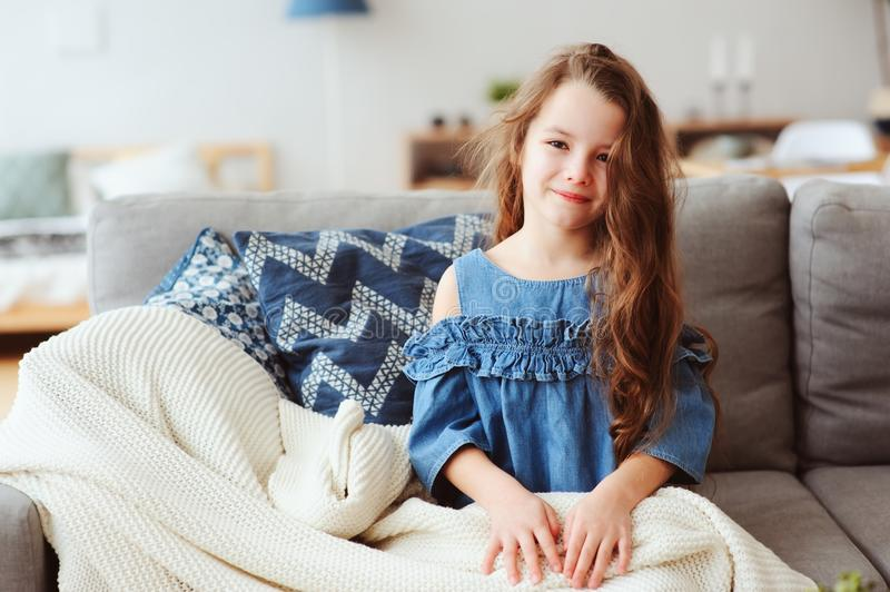 cute little child girl relaxing at home, sitting on couch, wrapped in cozy blanket stock image