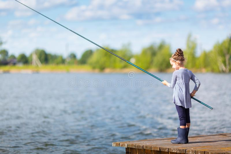 Cute little child girl in rubber boots fishing from wooden pier on a lake. Family leisure activity during summer sunny day.  stock photos
