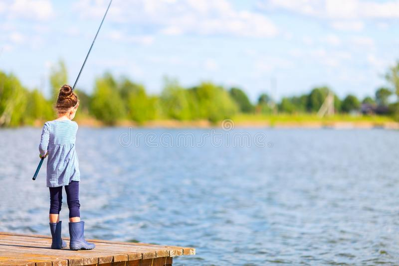 Cute little child girl in rubber boots fishing from wooden pier on a lake. Family leisure activity during summer sunny day royalty free stock images
