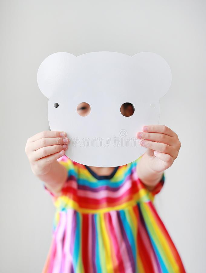 Cute little child girl showing blank white animal paper mask fronting her face on white background. Idea and concept for kid. Dressed up playing animal face stock photos