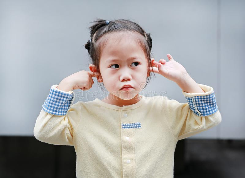 Cute little child girl shutting down her ears, holding her hands covers ears not to hear royalty free stock photos