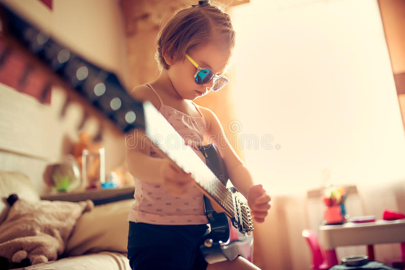 Cute little child girl in sunglasses playing guitar. royalty free stock images