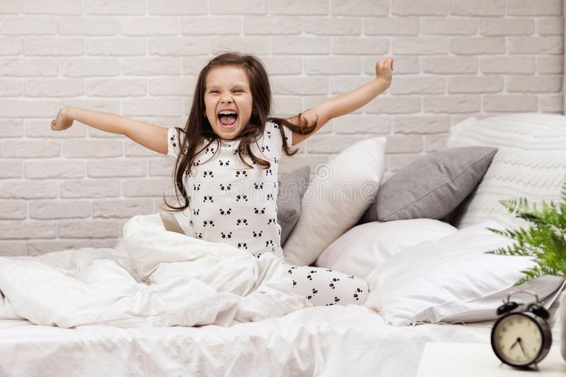 Cute little child girl wakes up from sleep. In bed in the morning stock photos