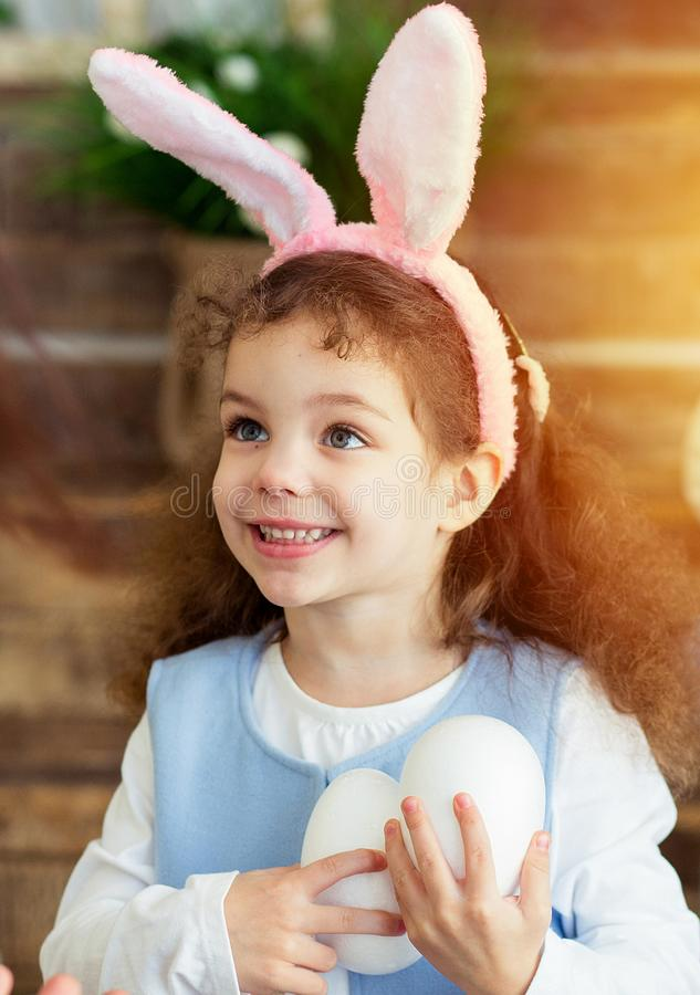 Cute little child girl wearing bunny ears on Easter day. Girl holding basket with painted eggs. stock images