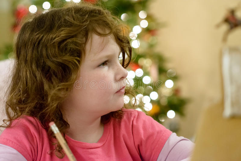 Cute little child girl writes the letter to Santa Claus near Christmas tree indoors. stock photos