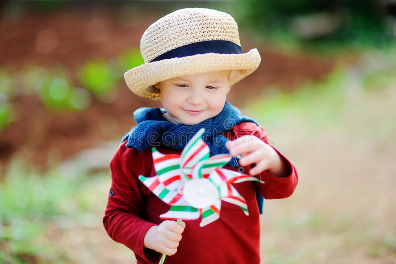 Cute little child holding toy windmill royalty free stock photos