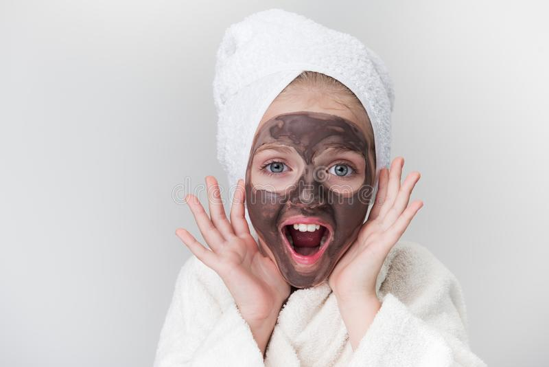 Cute little child is likes skincare treatment. Best result. Portrait of surprised pretty girl is standing with towel on head and white bathrobe and looking at royalty free stock photo