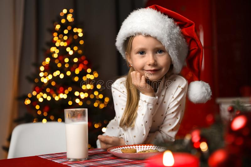 Cute little child with milk and cookies at table in room. Christmas time royalty free stock image