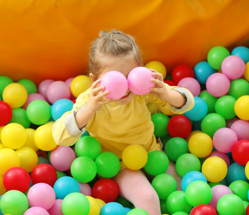 Cute little child playing in ball pit at amusement park. Cute little child playing in ball pit at indoor amusement park royalty free stock images