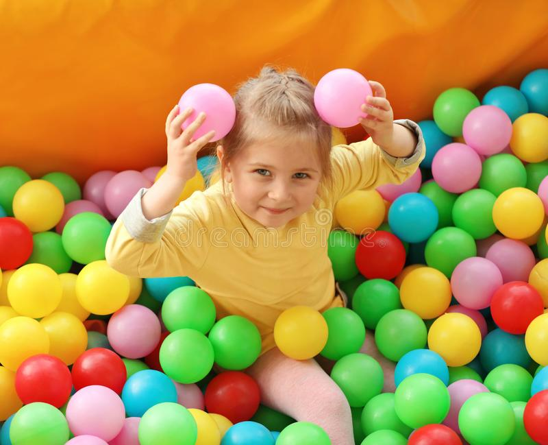 Cute little child playing in ball pit at amusement park stock image