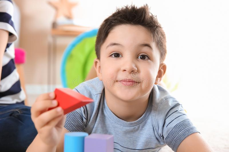 Cute child playing with building blocks, closeup stock photo