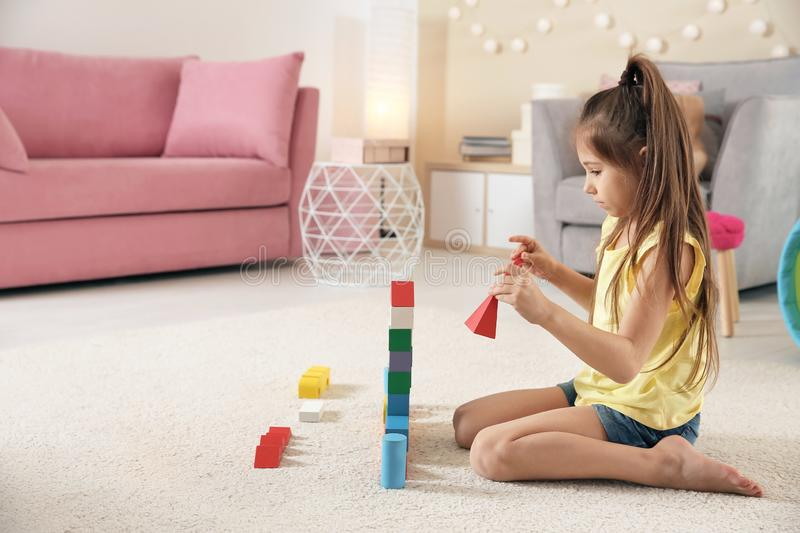 Cute little child playing with building blocks on floor. Indoors royalty free stock photos