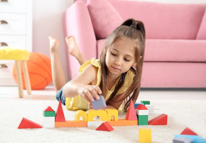 Cute little child playing with building blocks stock photos