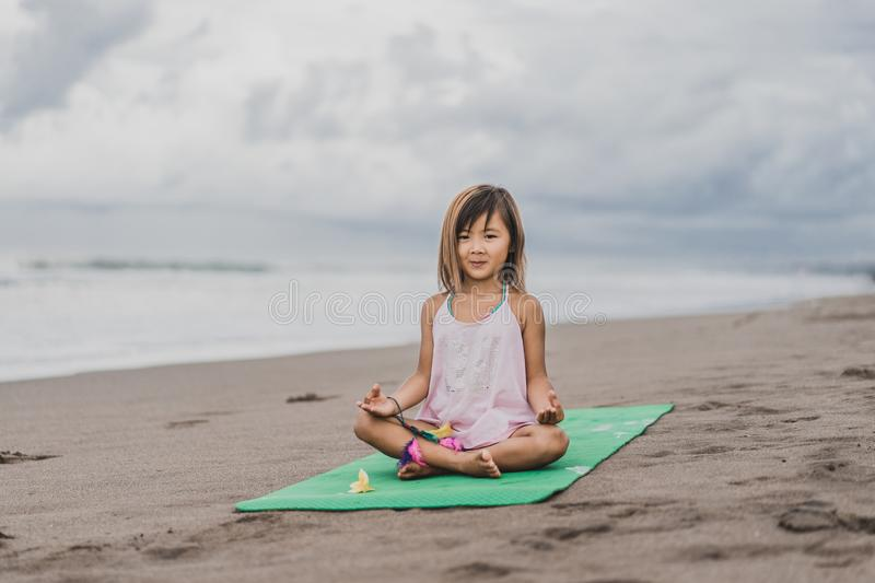 cute little child practicing yoga in lotus pose with gyan mudra stock images