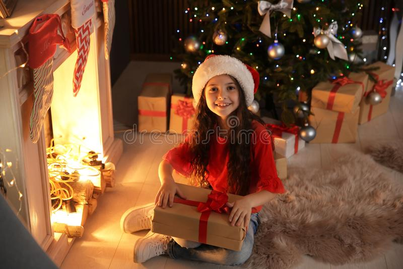 Cute little child in Santa hat with Christmas gift sitting in front of fireplace near fir tree stock photos