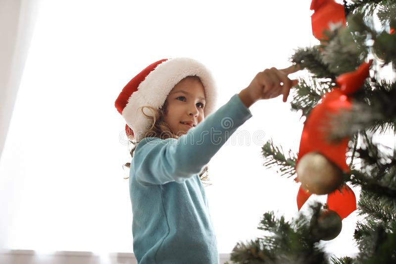 Cute little child in Santa hat near Christmas tree. At home stock photography