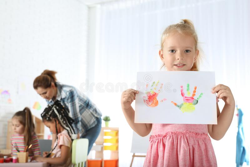 Cute little child showing sheet of paper with colorful hand prints. Painting lesson. Cute little child showing sheet of paper with colorful hand prints indoors stock photos