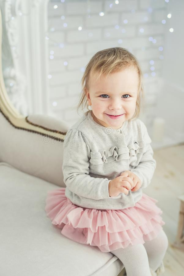 cute little child sitting in chair near Christmas tree. Happy new year. Portrait little girl. Christmas concept royalty free stock images