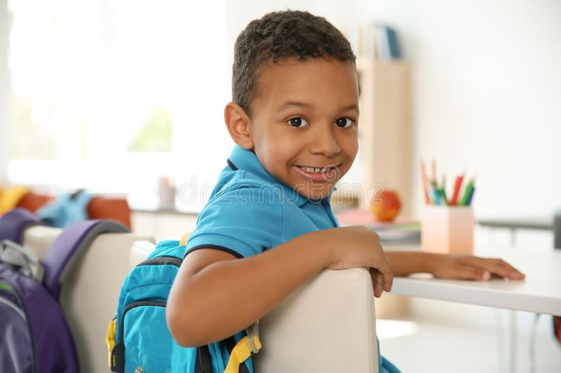 Cute little child sitting at desk in classroom. Elementary school royalty free stock photography