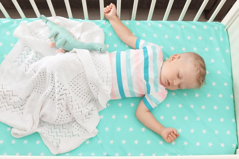 Cute little child sleeping in crib. At home stock photo