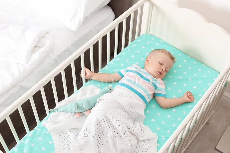 Cute little child sleeping in crib. At home stock image
