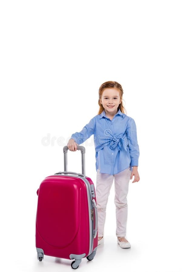 Cute little child standing with suitcase and smiling at camera. On white royalty free stock photos