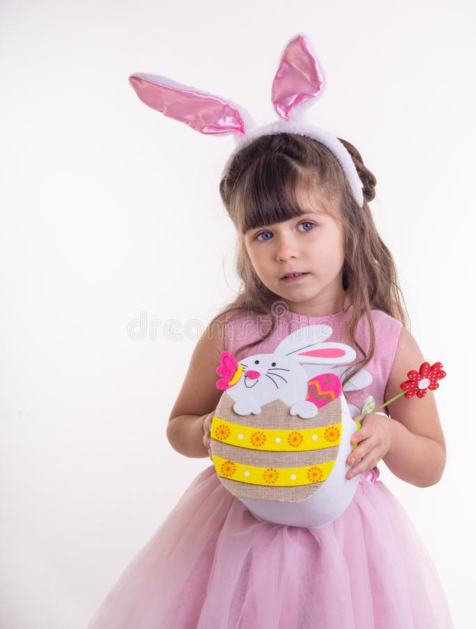Cute little child wearing bunny ears on Easter day. Girl holding basket with painted eggs. stock photo