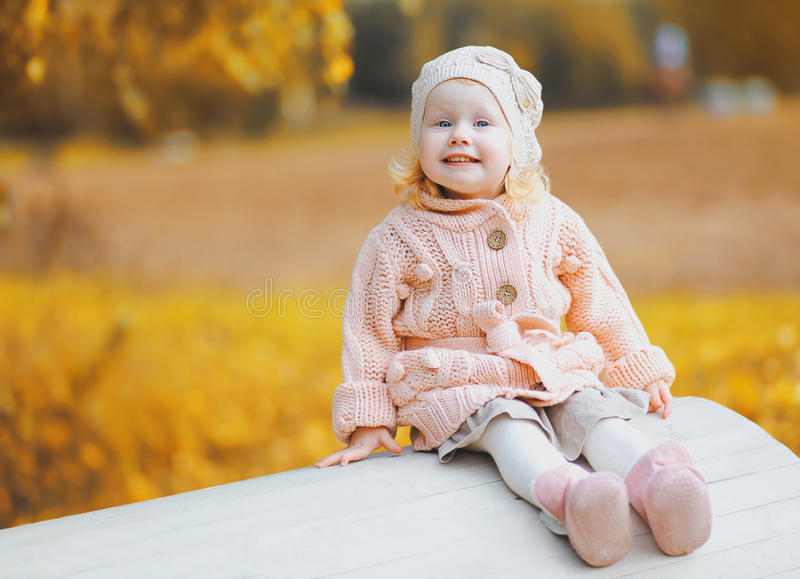 Cute little child wearing a knitted clothes having fun in autumn royalty free stock images