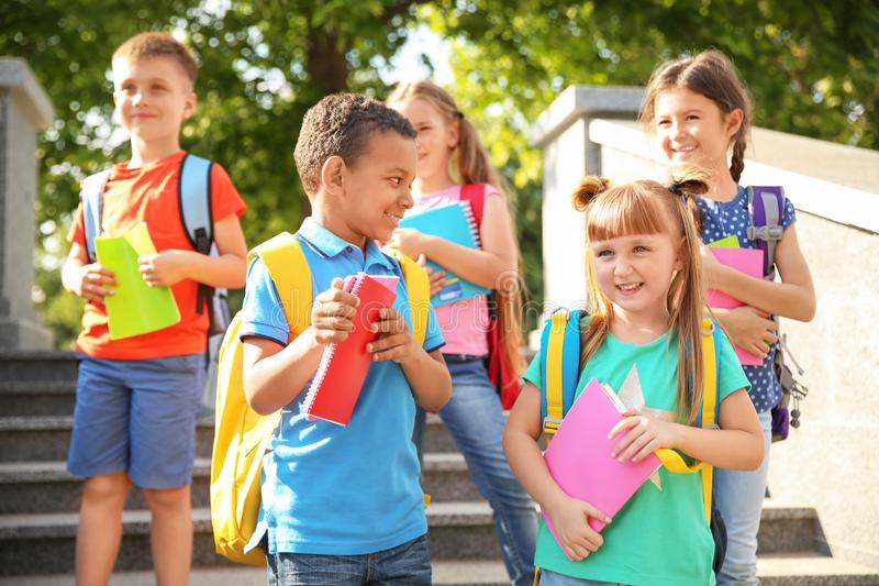 Cute little children with backpacks and notebooks outdoor. S. Elementary school royalty free stock photos