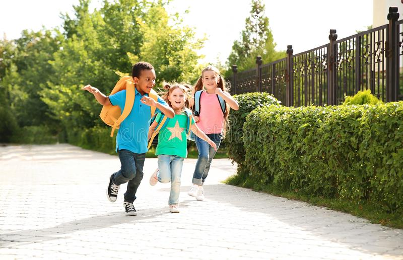 Cute little children with backpacks running stock photo