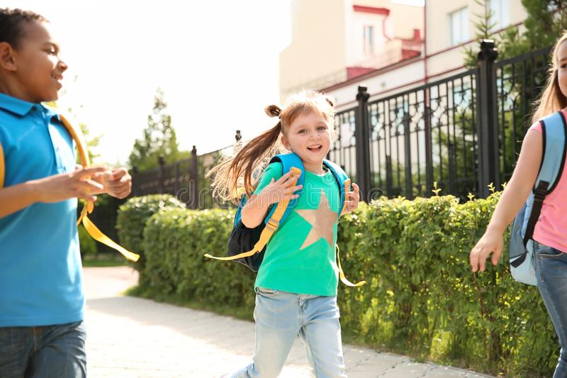 Cute little children with backpacks running outdoors. Elementary school royalty free stock photos