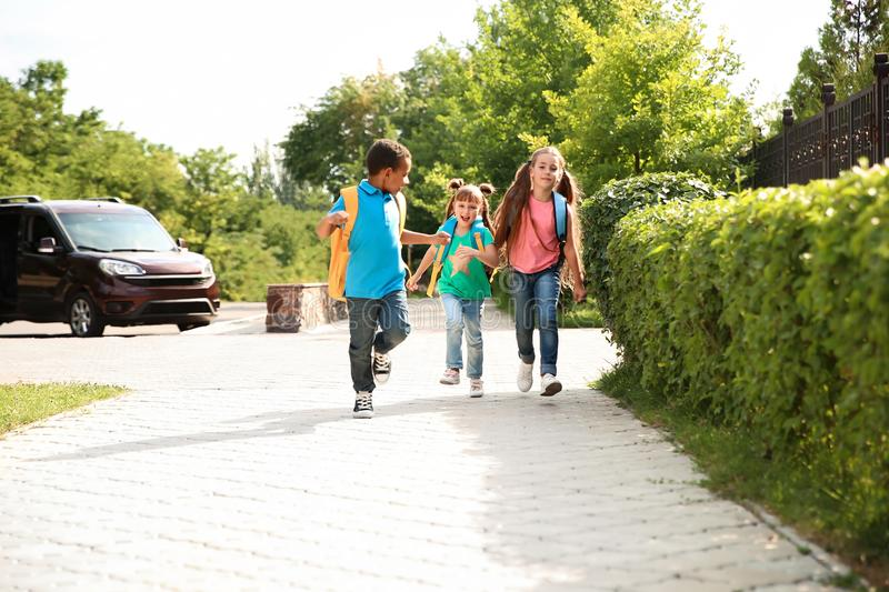 Cute little children with backpacks running outdoors. Elementary school royalty free stock photography