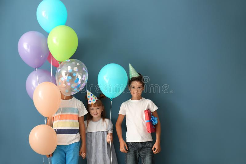 Cute little children in Birthday hats and with balloons on color background stock image