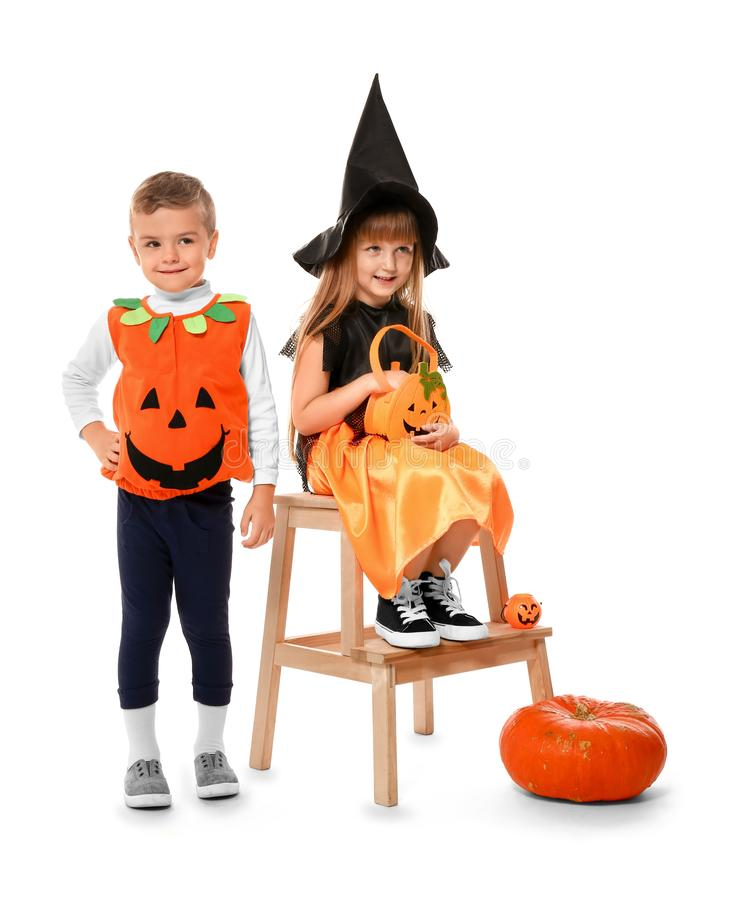 Cute little children dressed as witch and Jack-o-lantern for Halloween on white background royalty free stock photography