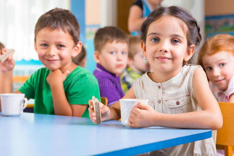Cute little children drinking milk. At daycare stock photo