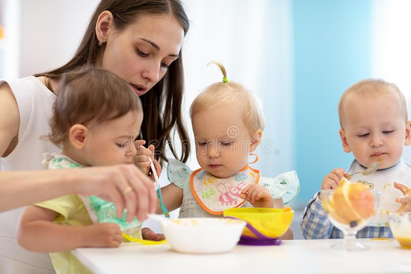 Cute little children eating healthy food at daycare centre royalty free stock photography