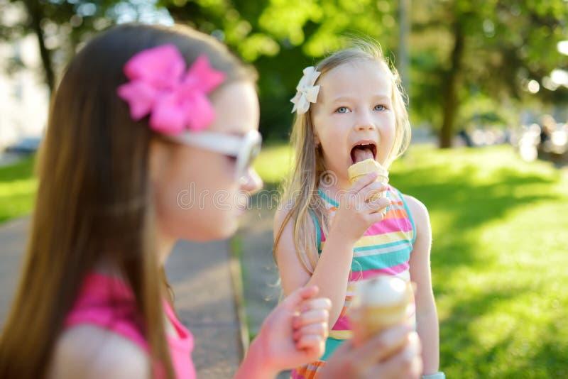 Cute little children eating tasty fresh ice cream in sunny summer park. Kids eating sweets stock photos