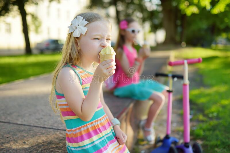 Cute little children eating tasty fresh ice cream in sunny summer park. Kids eating sweets royalty free stock photo