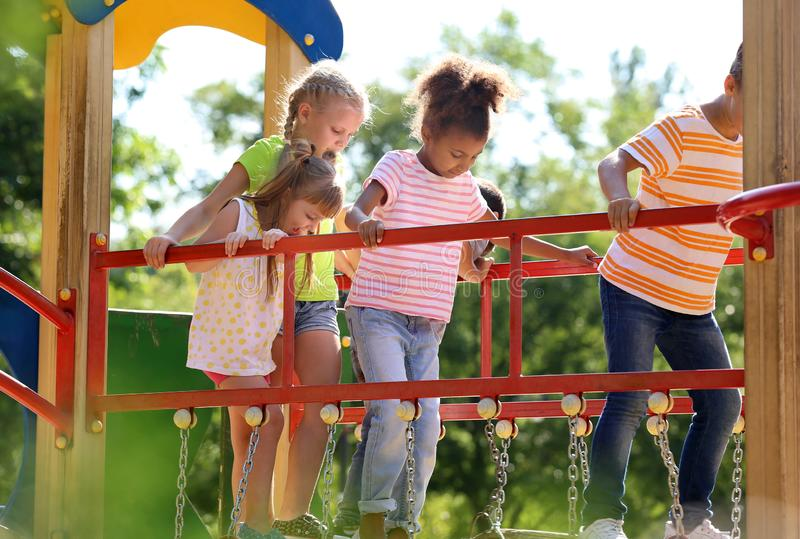 Cute little children having fun on playground outdoors royalty free stock photos