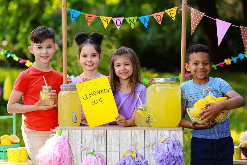 Cute little children at lemonade stand. Summer refreshing natural drink stock photos