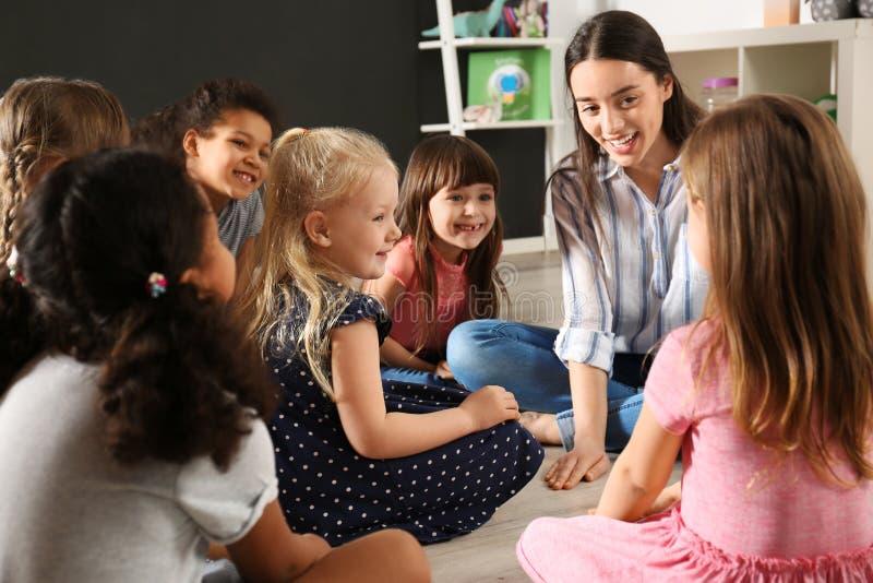Cute little children with nursery teacher in kindergarten royalty free stock photos