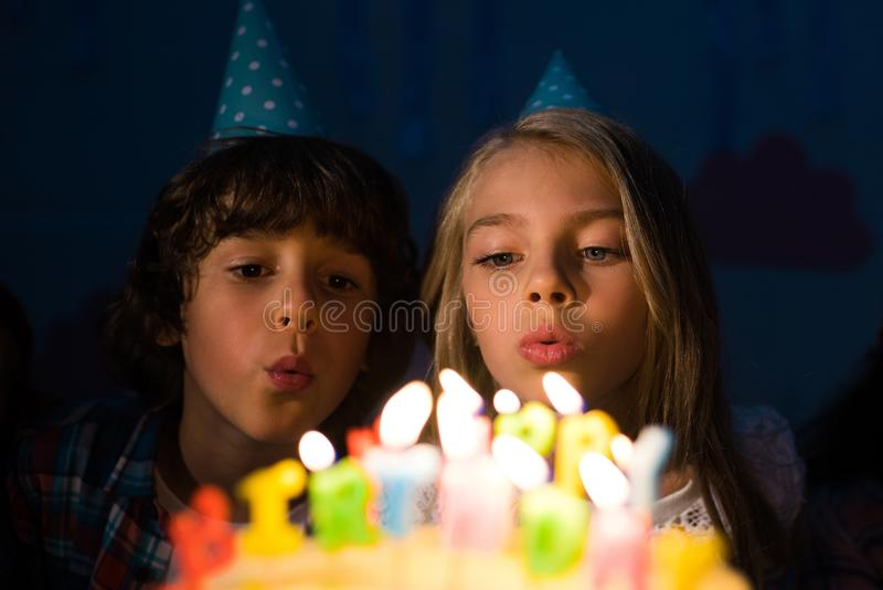 cute little children on party hats blowing candles stock images
