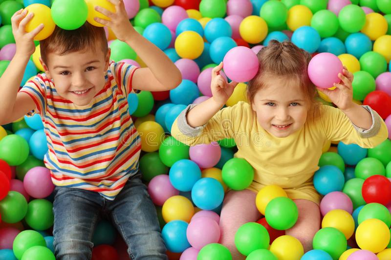 Cute little children playing in ball pit royalty free stock photography