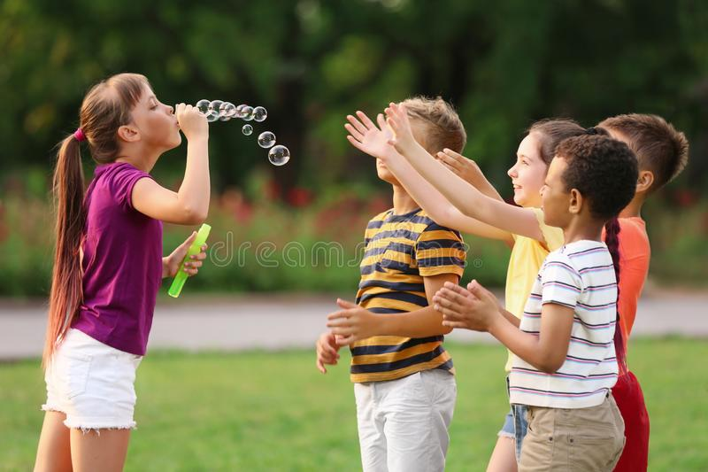 Cute little children playing with soap bubbles royalty free stock photography