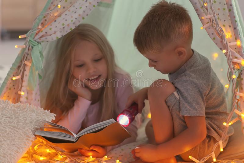 Cute little children reading book in hovel at home royalty free stock image