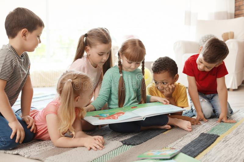 Cute little children reading book together indoors royalty free stock photography