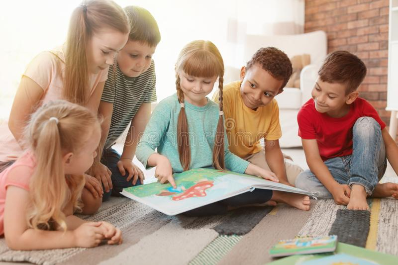 Cute little children reading book together. Learning by playing stock photo